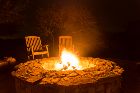 Fire flame in a fire pit and two empty wood chairs next to it with dark forest at the back Foto de archivo