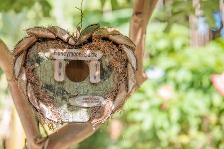 honeymoon suite: Honeymoon suite - wooden birds tree house in garden in a shape of heart waiting for just married Stock Photo