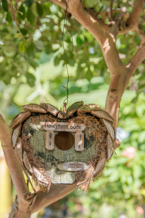 suite: Honeymoon suite - wooden birds tree house in garden in a shape of heart waiting for just married Stock Photo