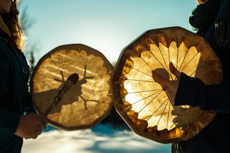 Vrouwen die hun heilige trommels in de winter buiten vasthouden en bespelen Stockfoto