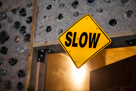 SLOW Sign fixed on an indoors doorframe. Home-made cob walls inlaid with decorative, recycled glass bottles