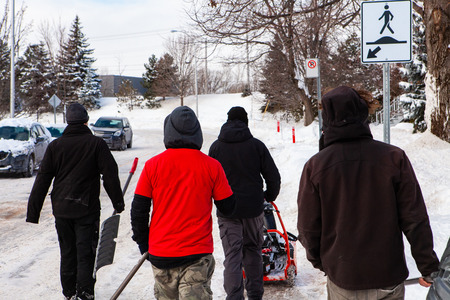 Men working as a snow removal team walking down the streets with shovels and snowblower to clear snow in front of houses after a winter storm, seen from behind