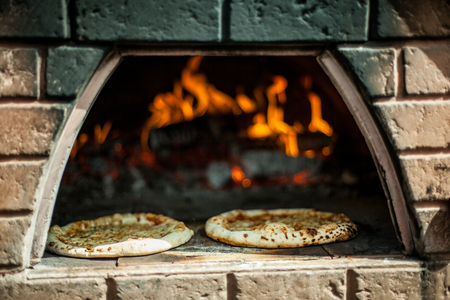 Two handmade pizzas being cooked in a bread oven at farmer's market Imagens