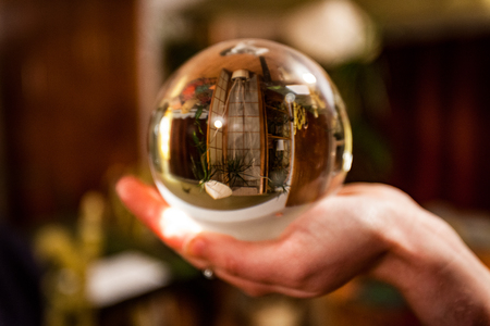 Hand holding a crystal ball in which appears the upside-down reflection of a living room full of plants Archivio Fotografico