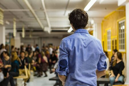 Conference in an industrial environment with yellow and white walls. Blurred audience mainly composed of young adults