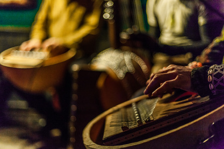 Man's hands playing kalimba with blurry musicians playing african instruments live on stage