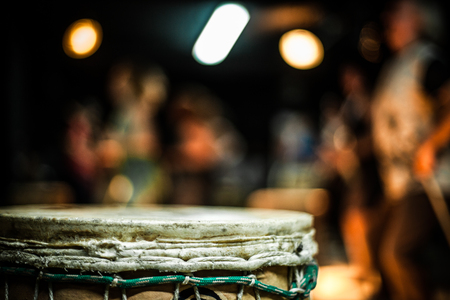 Close up of a djembe skin, with blurry drummers in the background