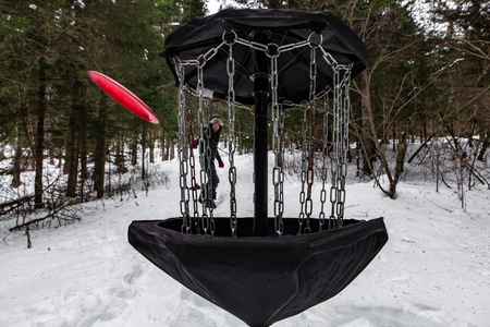 Man playing flying disk golf in the winter time