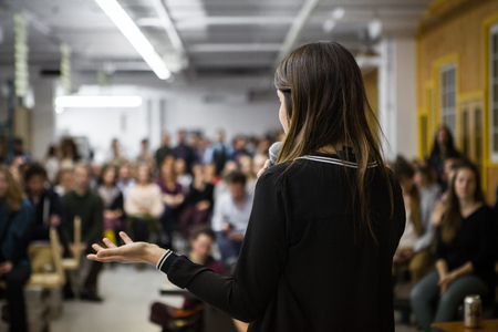 Woman gives a public speech in front of 200 people, in an industrial environment Stock Photo