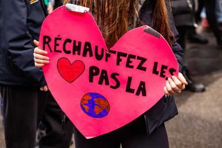 Environmentalist holds handmade sign. A french placard saying warm the hearts not the planet is held by a girl as ecological demonstrators march for the environment in a city center
