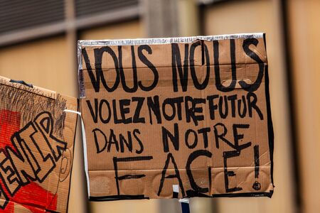 French placard held at ecological rally. A French sign saying you rob us of our future in our face is held by an environmental protestor during a demonstration in Montreal, Canada.