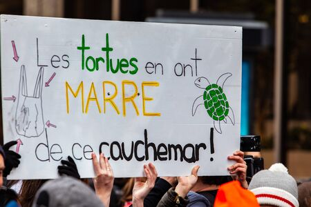 French sign at ecological demonstration. French words are written on a placard saying the turtles are fed up with this nightmare as ecological activists march against ocean pollution and climate change Stok Fotoğraf