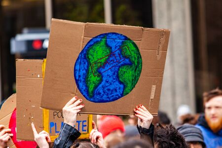 Protestors march for environment. A closeup view of a cardboard sign with a hand drawn picture of planet earth held up by an eco activist during a city center rally. Stok Fotoğraf