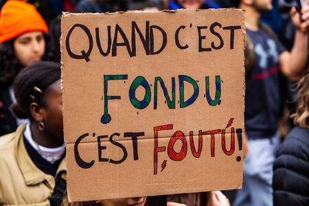 Ecological activist holds sign at rally. A closeup view of a French sign saying when its melted its fucked. Protestor holds message during a city street demonstration.