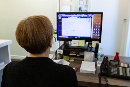La persona trabaja en la computadora en el escritorio de la oficina. Una vista de cerca de una trabajadora sentada en un escritorio de computadora concentrado en la pantalla de la PC. Parte posterior de la cabeza visible en un escritorio ocupado. El empleado del lugar de trabajo realiza tareas de TI. Foto de archivo