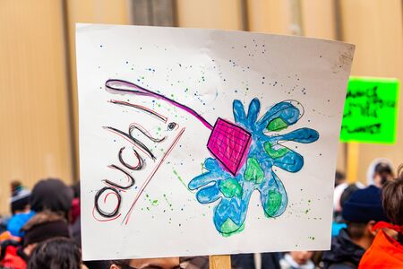 Poster held by ecological activist. A fly swatter squashing planet earth and the word ouch is drawn on a sign held be an environmental campaigner during a march on an urban city street.