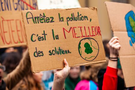 French placard at ecological protest. A closeup view of a French placard saying stop the pollution, its the best solution, is held by an environmentalist during a demonstration in Montreal, Canada.