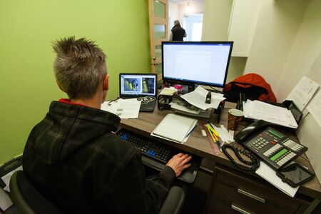 Man sitting at office desk with computer. An over the shoulder view of a male office worker sitting at a busy workstation. Messy desk with lots of paperwork and IT equipment. Concentrating on work task.