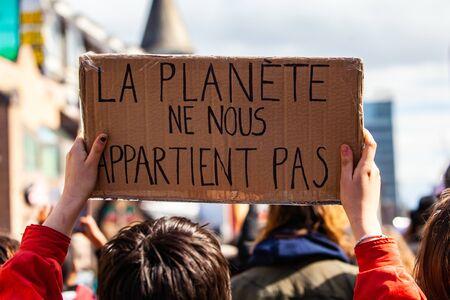Umweltaktivist hält französisches Zeichen. Eine Nahaufnahme eines Umweltschützers, der ein Pappschild mit den französischen Worten hält, der Planet gehört uns nicht, der in einer Menge von Demonstranten steht.