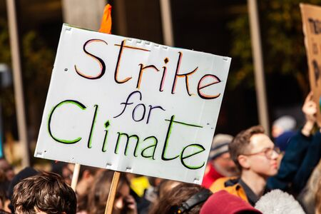 A cardboard placard is seen close-up on a crowded street of environmental activists, saying strike for climate, during a street demonstration.