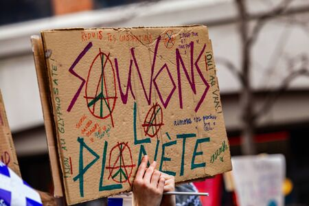 A French sign is viewed closeup during an environmental rally, saying save the planet and depicting the peace symbol, as protestors march in a city street.