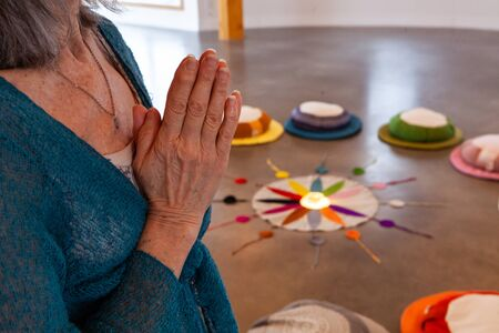 Hands of a religious person are seen closeup, held together as she prays in a peaceful room, twelve colors of the Native American circle are seen in background.