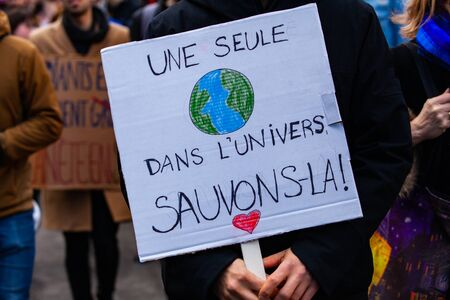 A French poster is viewed close up, saying only one in the universe, let's save it, held by an eco-activist during a march against climate change