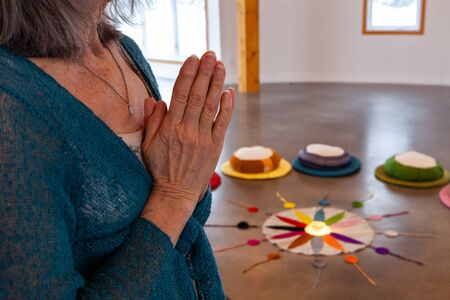 A closeup and side view on the wrinkled hands of an elderly spiritual lady, as she meditates close to the Native American color wheel.