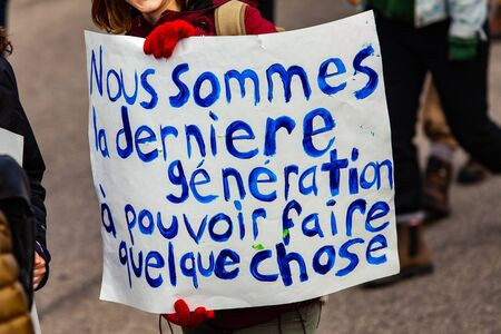 A close-up view of a French poster, saying we are the last generation to be able to do something, held by an environmental demonstrator during a city march.