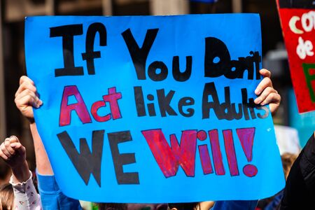 A colorful poster is seen close-up, held in the hands of an environmentalist, saying if you don't act like adults, we will, during a street demonstration