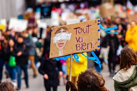 A homemade French placard is viewed close up, depicting a man blinded by money and the words everything is fine, as a crowd of environmentalists stage a rally.