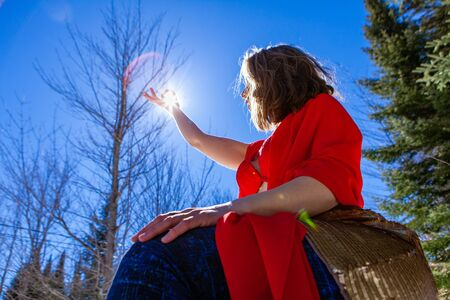 A low angle view of a sensual young woman holding a zen mudra hand gesture towards a bright sun. She meditates alone outdoors in woodland. Calm and concentrated