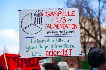 A French poster depicts the amount of household waste and says we must change our priorities, held by an activist during an environmental protest