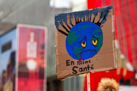 A French poster depicts a poorly planet earth and says healthy, viewed closeup during a march against global warming in the city