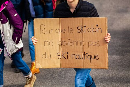 A closeup view of a homemade French sign, saying so that alpine skiing does not become water skiing, held by an environmentalist as protestors march for climate Stok Fotoğraf