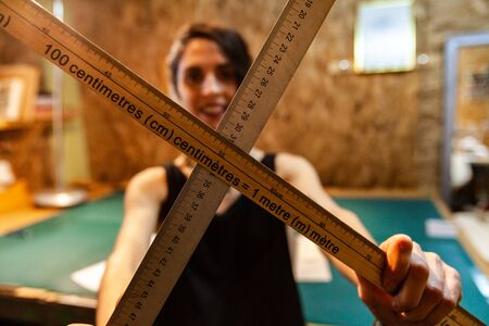 A female clothes maker is standing inside her vintage workshop, holding two wood measuring sticks. Artisan shows tools of trade.