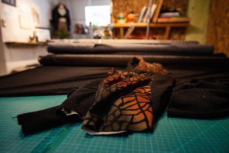 Patterned orange and black textiles, viewed close up, on the workbench inside a fashion workshop. Rolls of material ready for dressmaking.