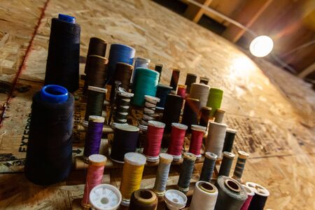A closeup view of colorful thread spools hanging on a wooden wall inside a fashion workshop. Different sizes hanging at a workstation.
