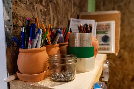A close up view of stationery pots filled with pens and pencils on a bookshelf with notebooks inside a fashion artists studio.