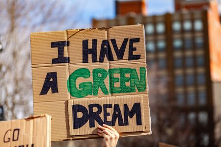 A protestor holds a cardboard sign, reading I have a green dream, viewed close-up as people unite against global warming in a city center.