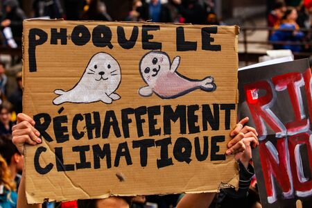 A close-up view of a French placard depicting two seals and the words seal global warming, as environmentalists unite against climate change in a city center. 免版税图像