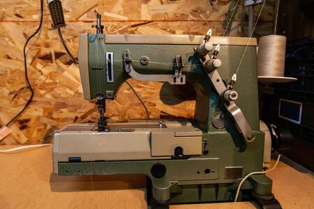 A closeup and side profile view of a retro sewing machine with thread spool inside a rustic studio. Recycled and working vintage machine used by eco dressmaker.