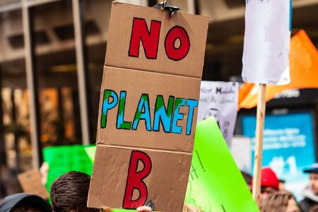 A cardboard poster is seen close-up, saying there is no planet b, held by an eco-activist during a demonstration on a street in Montreal, Canada Imagens