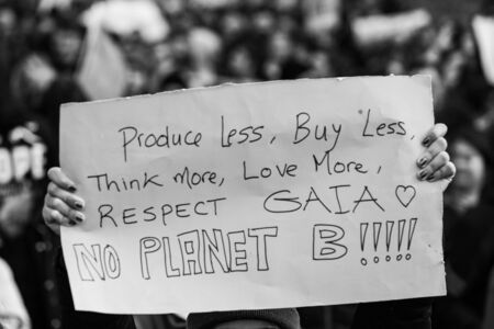 A closeup and monochrome view of a poster saying produce less, buy less, think more, love more, respect Gaia, no planet b, held by an ecological activist