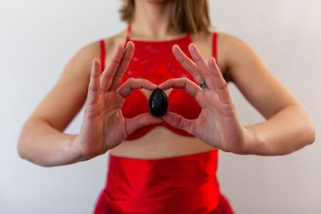 A sacred yoni nephrite egg is seen close-up, in the hands of a stunning young female wearing red lingerie, ancient stone object used to promote wellness.
