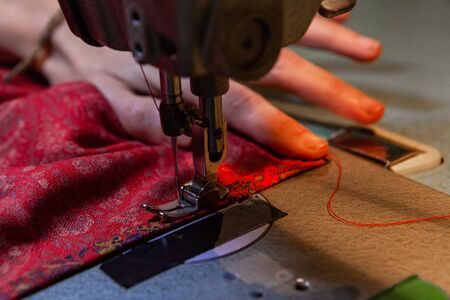 A closeup view of an eco-friendly fashion designer using a vintage sewing machine to stitch the edge of patterned fabric. Sewing machine needle with red thread.