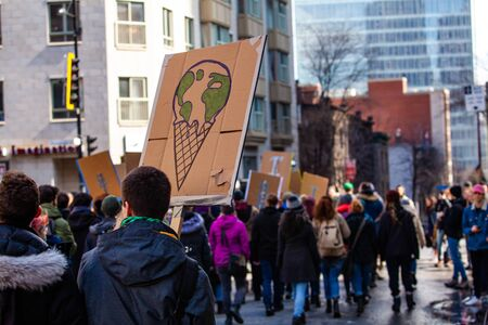 A close up view of a homemade cardboard sign showing planet earth melting on an ice cream cone as a crowd of ecological demonstrators march for the environment. Imagens