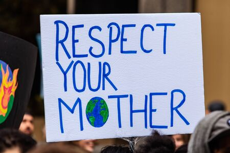 Protestors are viewed close-up, holding a poster saying respect your mother with a picture of planet earth, as they march for the environment in a city center