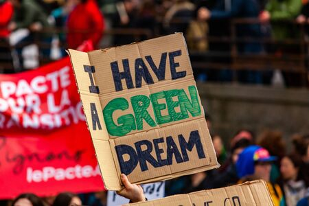 A homemade poster is viewed closeup, saying I have a green dream, as environmental demonstrators stage a peaceful protest in a city center. Imagens