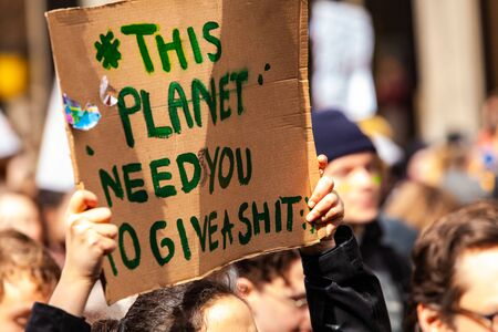 A cardboard sign is viewed closeup, saying this planet needs you to give a shit, among a crowd of activists marching for the environment in a city center